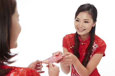 toothy: Young woman giving red envelope to friend LANG_EVOIMAGES