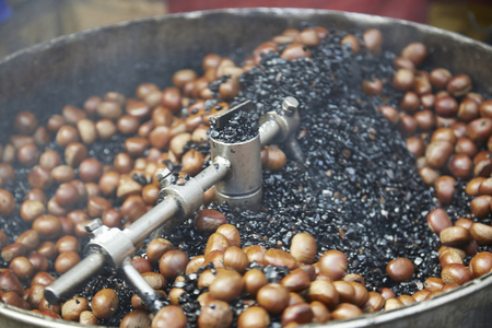 Chestnuts (castanea sativa) being cooked in hot metal pot