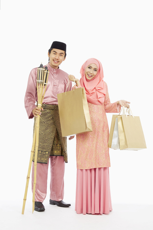 pelita: Husband and wife in traditional Malay clothes with shopping bags and Pelita torch LANG_EVOIMAGES