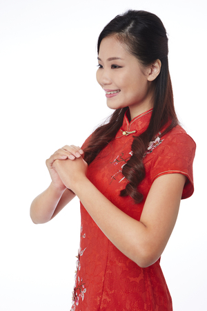 toothy: Young woman in traditional Cheongsam greeting good wishes LANG_EVOIMAGES