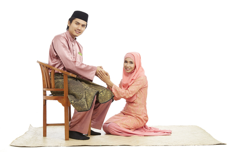Wife greeting husband with the Salam greeting gesture, both in traditional Malay clothes