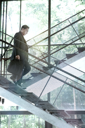 superiors: Businessman walking down the stairs in office