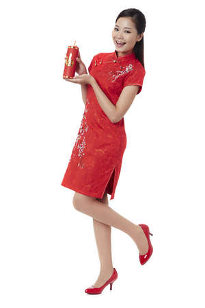 Young woman in traditional Cheongsam with firecracker LANG_EVOIMAGES