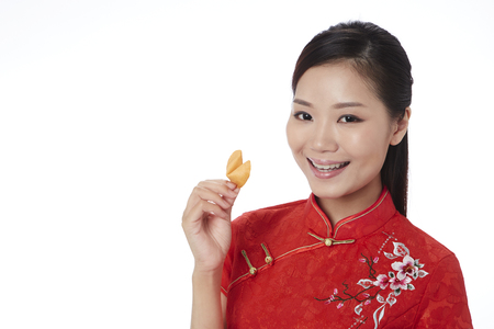 lucky charm: Happy woman holding a fortune cookie LANG_EVOIMAGES
