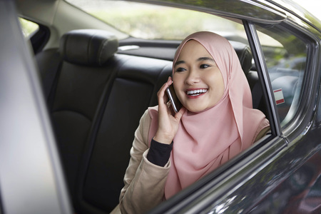 transportation: Young Malay woman talking on the phone in a car