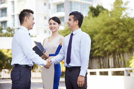 Two businessmen shaking hands while businesswoman stands nearby
