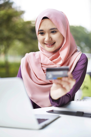 outerwear: Smiling young Malay woman using laptop for online shopping LANG_EVOIMAGES