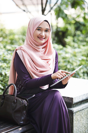 outerwear: Smiling young Malay woman using digital tablet at a park