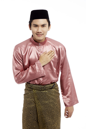 Man in traditional Baju Melayu with hand on chest