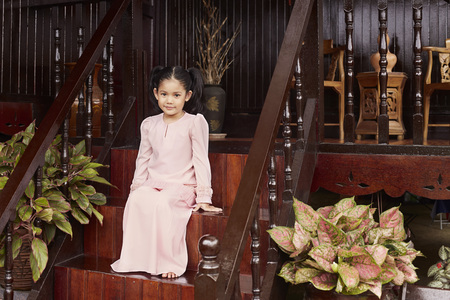 malay village: Girl sitting on porch steps LANG_EVOIMAGES