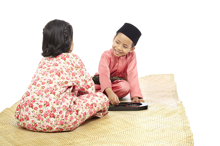 Boy and girl in traditional Malay clothes playing Congkak (traditional Malay board game)