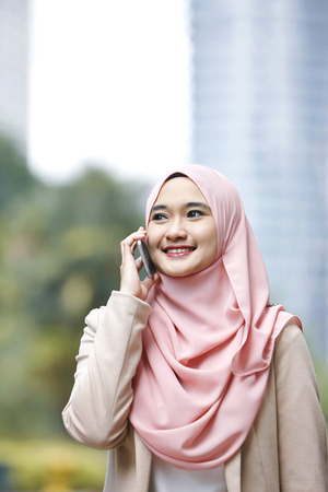 outerwear: Smiling young Malay woman talking on the phone