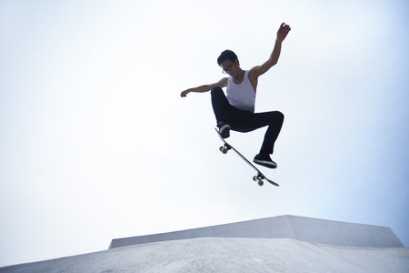 Young man doing skateboarding trick at a skate park LANG_EVOIMAGES
