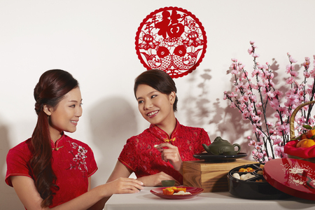 titbits: Young women having snacks during Chinese New Year celebration