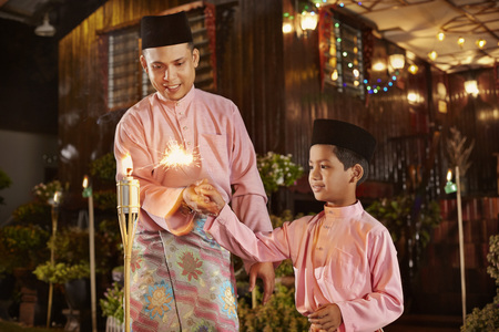 oil lamp: Father accompany his son to play with sparklers