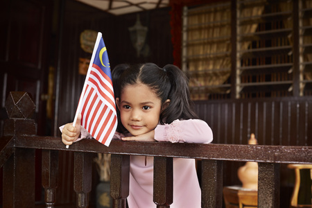 Young girl in traditional clothing smiling and holding a Malaysian flag LANG_EVOIMAGES