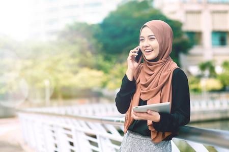well dressed: Smiling young woman talking on the phone while holding tablet