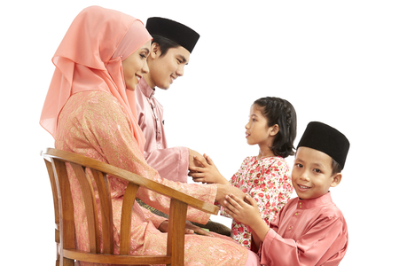 Children greeting parents with the Salam greeting gesture on Hari Raya
