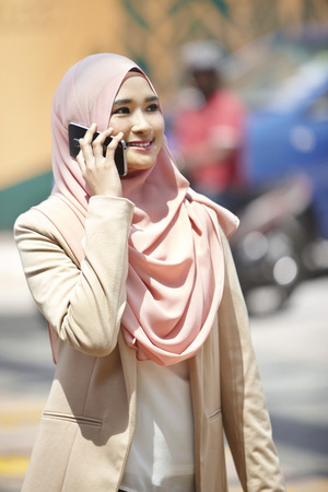 people: Smiling young Malay woman talking on the phone