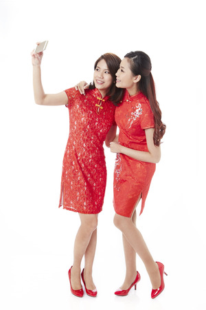 Young women in traditional Cheongsam taking selfie LANG_EVOIMAGES