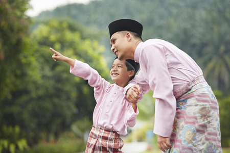 Father and son holding hands and pointing at something outdoor during Hari raya
