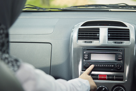 road shoulder: Woman switching on radio in car