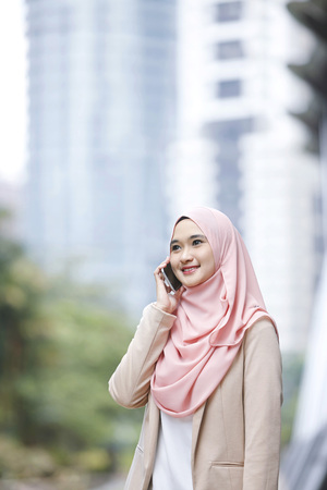 Smiling young Malay woman talking on the phone