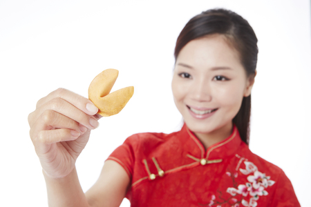 Happy woman holding a fortune cookie LANG_EVOIMAGES