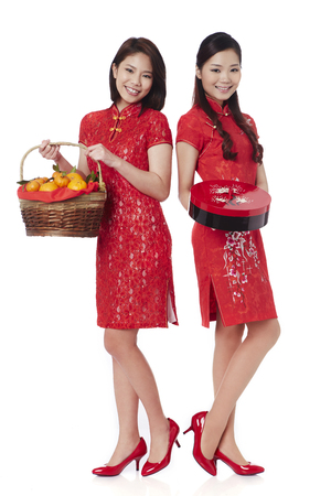 Young women holding gift box and mandarin oranges in a bamboo basket