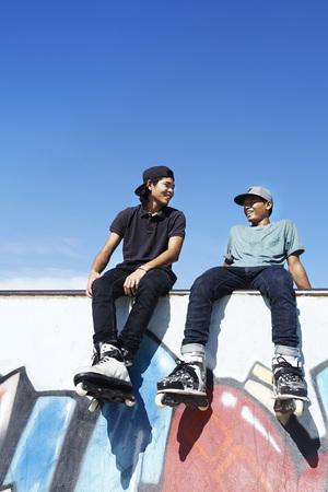skate park: Young men sitting at a skate park