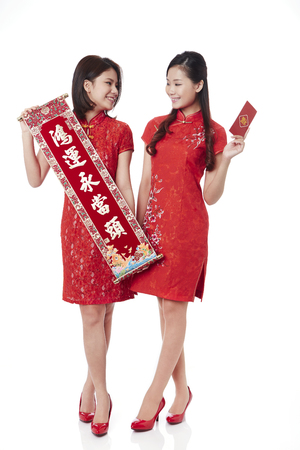 Young women in traditional Cheongsam holding banner with Chinese New Year greetings and red envelopes
