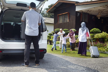 malay village: Senior couple greeting family members at home yard