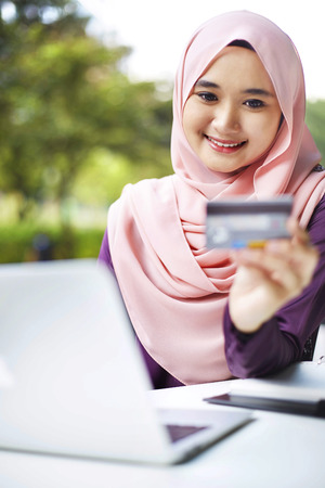 Smiling young Malay woman using laptop for online shopping LANG_EVOIMAGES