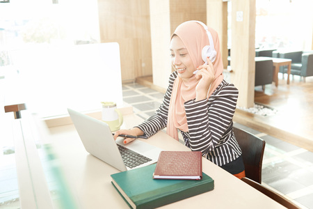 Smiling young businesswoman using laptop while wearing headphone in the office
