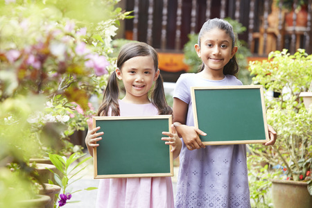 multi age: Young girls holding blank chalkboard LANG_EVOIMAGES
