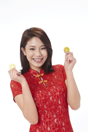 lucky charm: Young woman in traditional Cheongsam holding Chinese golden coin LANG_EVOIMAGES