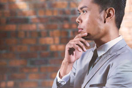 well dressed: Young businessman holding chin in hand while looking away