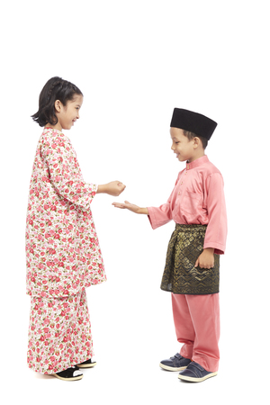 preadolescent: Boy and girl in traditional Malay clothes playing paper-rock-scissors