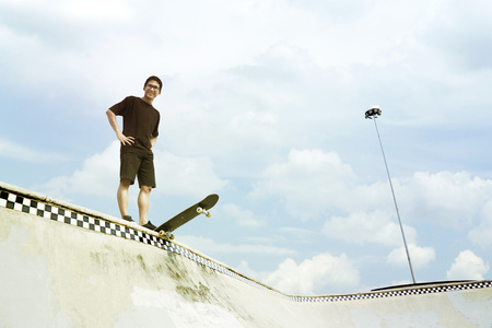 Young man looking at camera while standing on a skateboard at a skate park