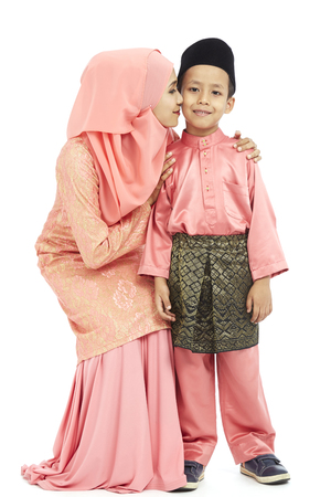 Mother kissing son on the cheek, both in traditional Malay clothes
