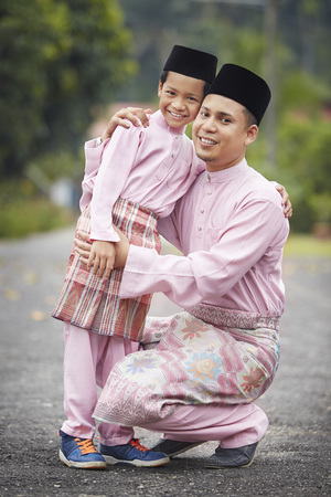 Father and son embracing outdoors during Hari raya