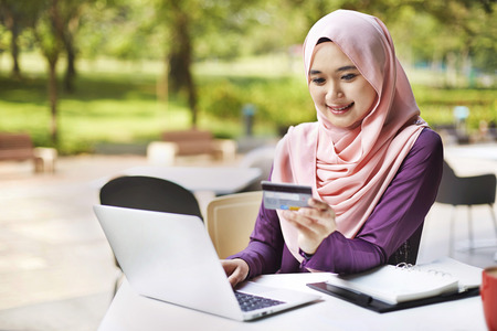 people: Smiling young Malay woman using laptop for online shopping LANG_EVOIMAGES