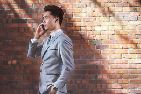 well dressed: Young businessman with hand in pocket talking on the phone