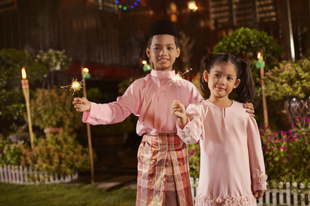 looking away from camera: Kids play with sparklers on Hari Raya