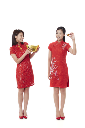 Young women in traditional Cheongsam holding gold ingot LANG_EVOIMAGES