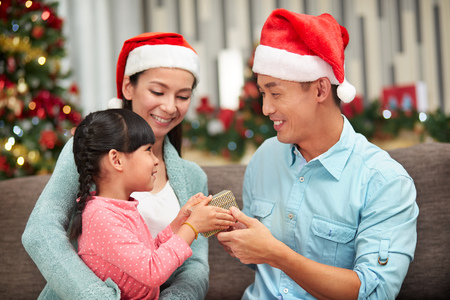 Man in Santa Claus hat holding gift LANG_EVOIMAGES