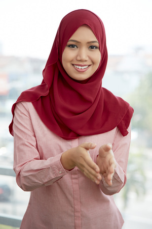 Businesswoman with hands in Salam greeting gesture