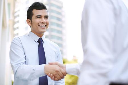 Two businessmen shaking hands outdoor