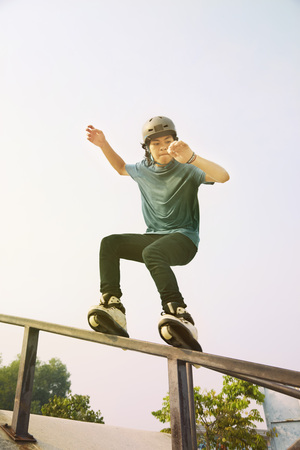 Young man inline skating on top of railing at a skate park