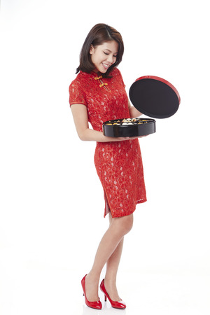 Young woman in traditional Cheongsam holding an assorted tasty treats box